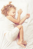 Lovely little boy lying in bed Stock Photos