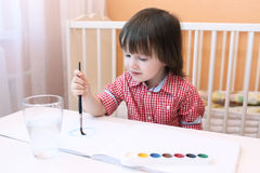 Lovely little boy paints with water color Stock Photo