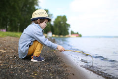 Lovely little boy plays with stick on riverside Royalty Free Stock Images