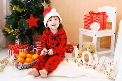 Lovely little boy in Santa hat with lollipop and presents sits n Stock Image