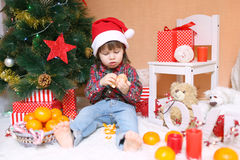 Lovely little boy in Santa hat with tangerine Royalty Free Stock Photos