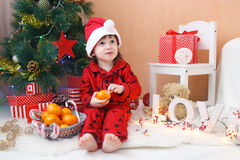 Lovely little boy in Santa hat with tangerines. Lovely little boy in Santa hat with tangerine sits near Christmas tree Stock Photo