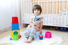 Lovely little boy sitting on potty at home. Lovely little 2 years boy sitting on potty at home stock image