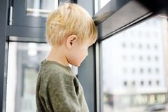 Lovely little boy sitting on the window near panoramic window and looking outside Royalty Free Stock Photo