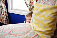 Lovely little boy in striped jumper playing hide and seek in the house royalty free stock photography