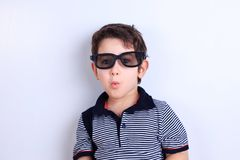 Lovely little boy in sunglasses blowing a kiss, studio shoot on stock images