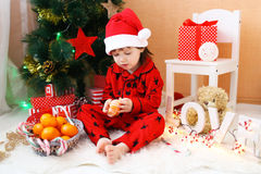 Lovely little boy with tangerine sits near Christmas tree Royalty Free Stock Photography