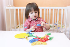 Lovely little boy (2.5 years) plays with clothes pins Stock Photography