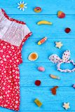 Lovely little casual kids dress. Textile dress for little girls and accessories, blue wooden background. Little kids summer look Stock Photo