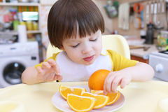 Lovely little child eating orange Stock Photos