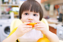 Lovely little child eats orange Stock Images