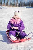 Little girl in bob-sleigh enjoying winter time. Lovely little child in purple overall sitting in bob-sleigh Royalty Free Stock Photography