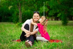 Lovely little daughter kiss mother. Outdoor Portrait of happy family. Happy Mother`s Day Joy. royalty free stock photography