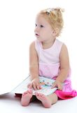 Lovely little girl with bare feet sitting on the Stock Images