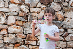 Lovely little girl blowing soap bubbles. Stones background Stock Photography