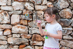 Lovely little girl blowing soap bubbles Stock Image