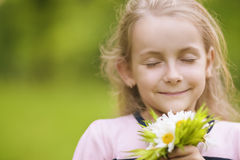 Lovely little girl breathing flowers Royalty Free Stock Photo