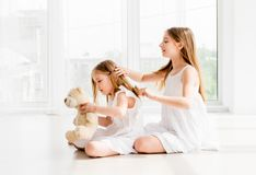 Lovely little girl brushing hair of younger sister royalty free stock photography