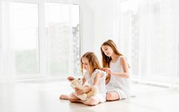 Lovely little girl brushing hair of younger sister stock photography