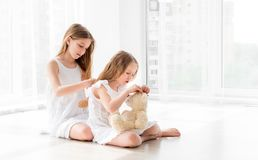 Lovely little girl brushing hair of younger sister stock photos