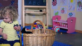 Lovely little girl child put all toys into wicker basket. Kid tidy clean up room