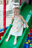 Lovely little girl on a children's slide Royalty Free Stock Images