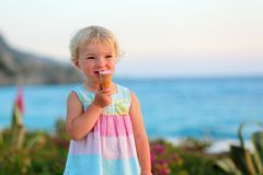 Lovely little girl eating ice cream on the beach Stock Images