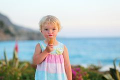 Lovely little girl eating ice cream on the beach Royalty Free Stock Photo