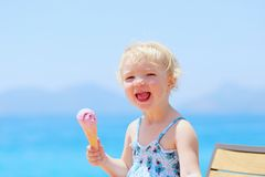 Lovely little girl eating ice cream on the beach Royalty Free Stock Photography