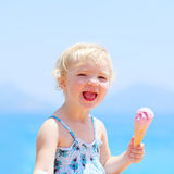 Lovely little girl eating ice cream on the beach Royalty Free Stock Image