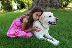 Lovely little girl with her best dog friend at park during summer in Michigan stock photo