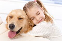 Lovely little girl and her pet dog. Lovely little girl hugging pet dog with passion, eyes closed Stock Photo