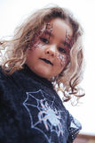 Lovely little girl looking at camera in Halloween. Little girl with spider web painted on face looking at camera. Halloween Royalty Free Stock Images