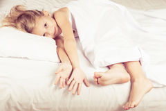 Lovely little girl lying on the bed Stock Photography