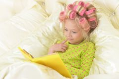 Lovely little girl with pink curlers reading stock photos