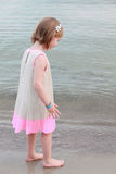A lovely little girl in a pink dress walking barefoot on the waves along the beach on a summer sunny day Royalty Free Stock Photography
