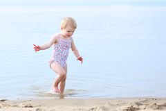 Lovely little girl playing on the beach Stock Images