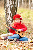 Lovely little girl playing guitar Stock Photo
