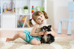 Lovely little girl playing with her pet dog stock photo