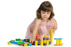 The lovely little girl plays colour wooden cubes Stock Image