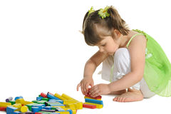 The lovely little girl plays colour wooden cubes Stock Photos