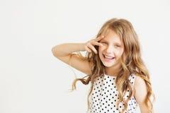 Lovely little girl in a polka-dot dress against a white backgrou Royalty Free Stock Photo