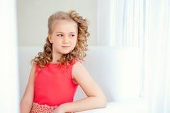 Lovely little girl posing in smart red dress Stock Photo