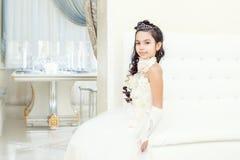 Lovely little girl posing in white luxurious dress Stock Photo