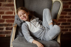 Lovely little girl reclines in chair with a smile upon the face. Little girl in soft gray pajamas reclines in chair with smile upon the face. She has retired to Stock Photography