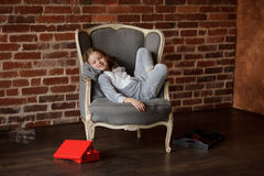 Lovely little girl reclines in a chair with a smile upon the face. Little girl in soft gray pajamas reclines in chair with smile upon the face. She has retired Royalty Free Stock Images