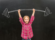 Lovely little girl rising up drawm barbell with two hands Stock Image