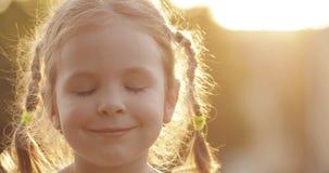 Lovely little girl smiling at camera in backlit sunlight.