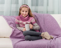 Lovely little girl on a sofa with warm blanket Stock Photo