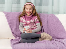 Lovely little girl on a sofa with warm blanket. Holding a cup of tea Stock Photography